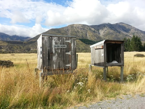 this picture shows two large boxes (on posts) beside the road in the Lewis Pass. Not sure what these boxes are used for perhaps for delivery or pick up of something in this rural area. It is the height of summer so the grass is long and brown