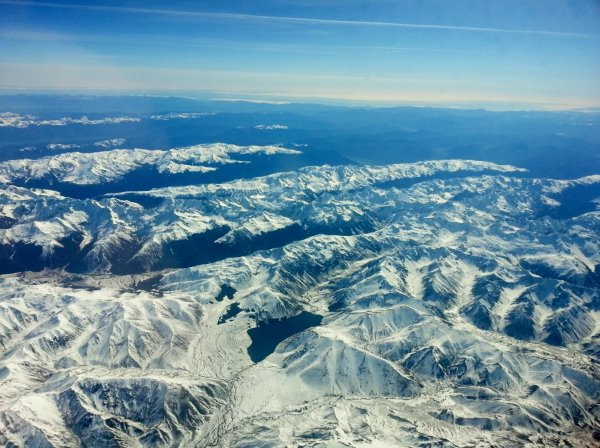 this pictures shows the mountains, covered in snow, from an airplane