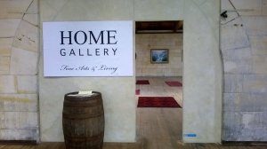 this picture shows the pseudo arch doorway to Home Gallery Fine Arts. A barrel is at the doorway and we can see a glimpse into the gallery